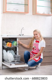 Smiling young blonde woman stacking dishware into dishwasher in kitchen with white background. Cheerful expression about housework
