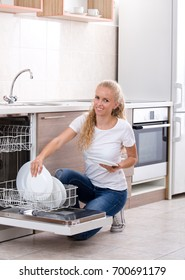 Smiling young blonde woman stacking dishware into dishwasher in kitchen. Cheerful expression about housework