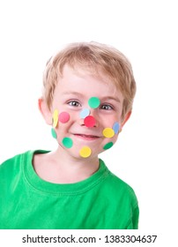 Smiling young boy with colorful round dot stickers on his face