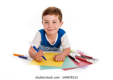 Smiling young boy with felt pens writing and drawing on  colorful paper. White background.