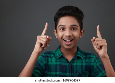 Smiling young boy with his index finger raised