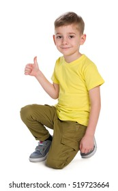 A smiling young boy with his thumb up is sitting on the white background