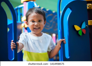 Smiling young boy holding on from a kids playground jungle gym with an excited look and ready to have fun.
