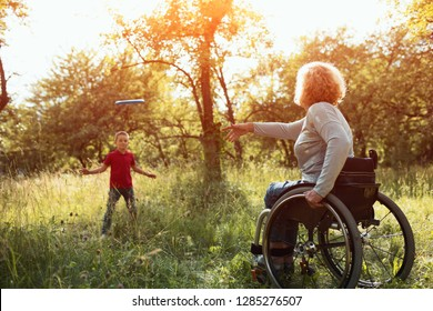Smiling Young Boy In Red T-Shirt Happily Catches The Frisbee From His Beautiful Disabled Mother Who Is Sitting In A Wheelchair. Family Rest. Disability And Happiness