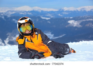 Smiling young boy skier on snowy mountain with helmet and face mask or goggles,