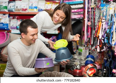 Smiling young boyfriend helping happy girl to choose bowl in pet store. Focus on guy