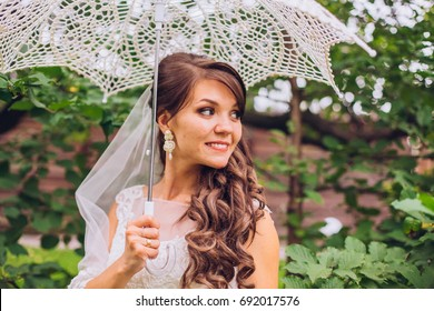 Smiling young bride portrait with umbrella in park.