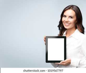 Smiling young brunette businesswoman showing blank no-name tablet pc monitor, over grey background, with copyspace area for slogan or text message. Success in business concept studio shot.