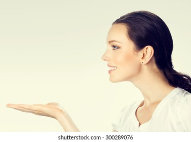 smiling young brunette businesswoman showing something or blank copyspase area for product or sign text message