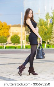 Smiling young brunette wearing black dress posing with handbag