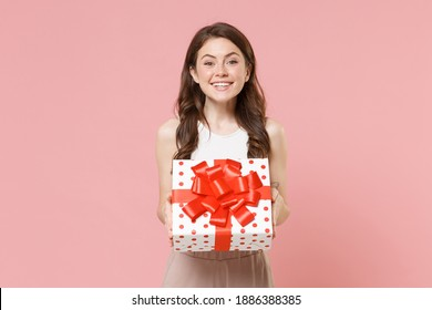 Smiling young brunette woman 20s in light casual clothes posing isolated on pastel pink wall background. Birthday holiday concept. Mock up copy space. Hold white red present box with gift ribbon bow