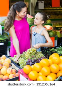 Smiling young brunette woman with girl in school age buying ripe grapes in supermarket