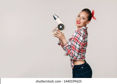 smiling young brunette woman with hair dryer. pin-up retro style. copy space for text