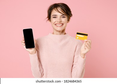 Smiling young brunette woman in knitted casual sweater isolated on pastel pink background. People lifestyle concept. Mock up copy space. Hold mobile phone with blank empty screen hold credit bank card