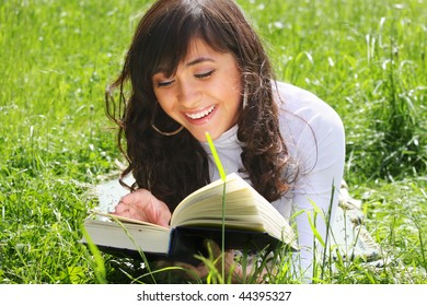 Smiling young brunette woman reading book on grass