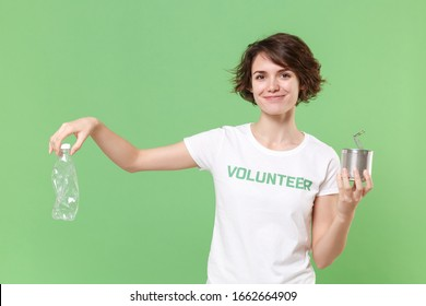 Smiling young brunette woman in volunteer t-shirt isolated on pastel green wall background. Voluntary free work assistance help charity grace teamwork concept. Hold trash empty plastic bottle, tincan