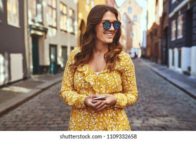 Smiling young brunette woman wearing sunglasses and holding her cellphone walking alone through the cobblestone streets of a city