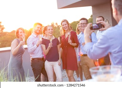 Smiling young business colleagues talking while standing at rooftop during party