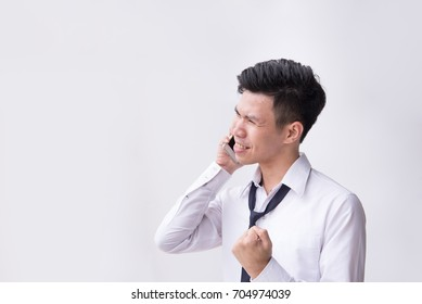 Smiling young business man being surprised as hearing message at smartphone in his hand with white background and copyspace.