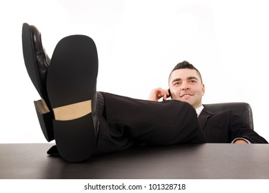 Smiling young business man relaxing at office desk and talking on mobile phone, isolated on white