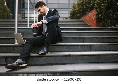 Smiling young business man sitting on steps with laptop and coffee. Relaxed entrepreneur looking at laptop and smiling while sitting on steps outside office.