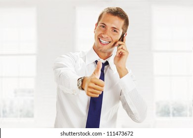 smiling young business man talking on the phone and making ok