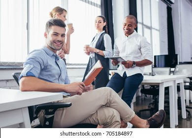 smiling young business people working and drinking coffee in office