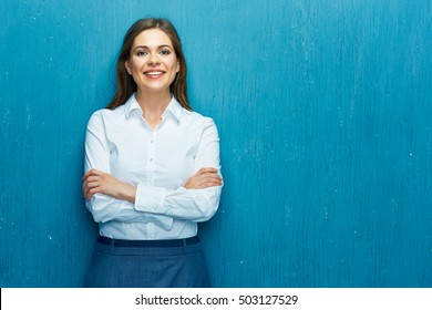 Smiling young business woman against blue wall. White shirt dressed.