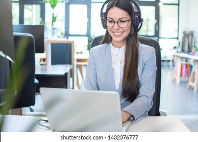 Smiling young business woman with headset using laptop in office