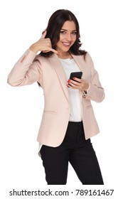 smiling young business woman making the call me sign while texting on her phone on white background