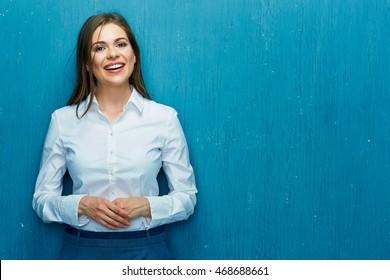 Smiling young business woman portrait on blue wall background. White shirt.