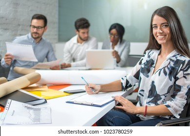 Smiling young business woman taking notes to clipboard while sitting in office with colleagues in the background.