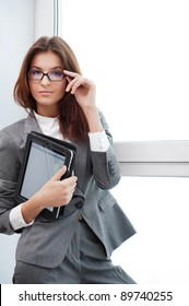 Smiling young business woman using tablet PC while standing relaxed near window at her office