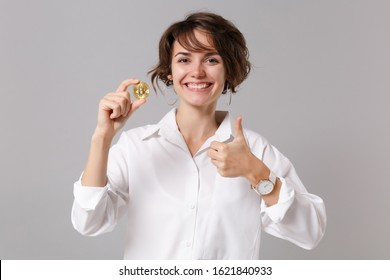 Smiling young business woman in white shirt posing isolated on grey wall background. Achievement career wealth business concept. Mock up copy space. Showing thumb up, hold bitcoin, future currency