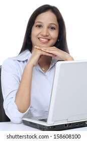 Smiling young business woman working with laptop against white