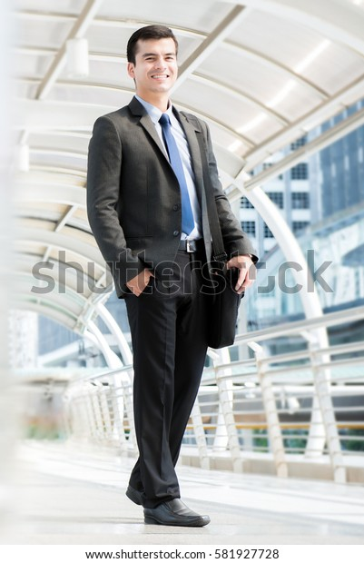 Smiling young businessman carrying bag while walking in outdoor covered walkway, full body