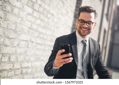 Smiling young businessman checking his smart phone