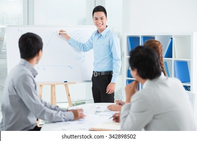 Smiling young businessman conducting presentation in front of his colleagues