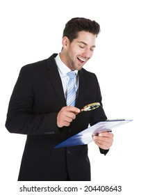 Smiling young businessman examining document on clipboard with magnifying glass over white background