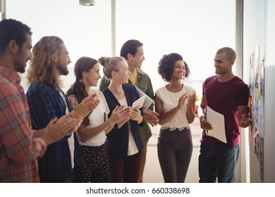 Smiling young businessman explaining to creative team standing at office