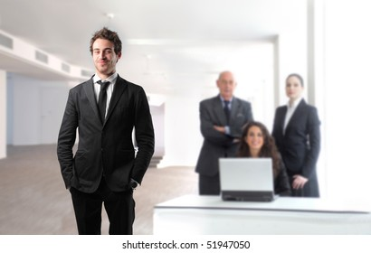 Smiling young businessman with group of business people on the background