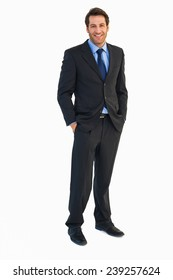Smiling young businessman with hands in pockets on white background