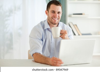 Smiling young businessman having a cup of tea