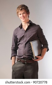 Smiling young businessman holding a laptop
