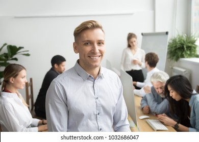 Smiling young businessman looking at camera with diverse team office people employees at background, business coach, successful team leader or professional executive manager head shot portrait