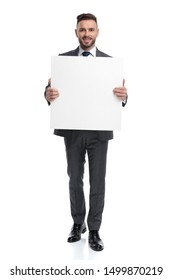 smiling young businessman showing a blank board isolated on white background