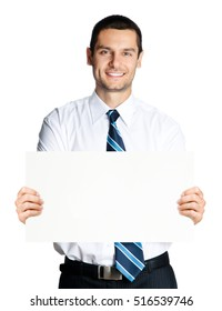 Smiling young businessman showing blank signboard, isolated on white background. Empty copyspace area for slogan or advertising text message. Success, business, job and education concept studio shot.