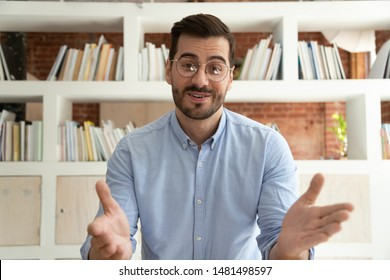 Smiling young businessman sit at desk talk on webcam having video call or conversation with client, motivated millennial male coach or trainer speak shoot online tutorial, record training course