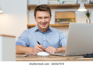 Smiling young businessman sitting at desk in office