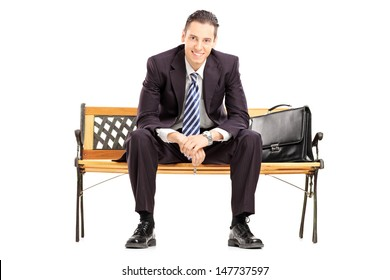 Smiling young businessman sitting on a wooden bench and looking at camera isolated on white background